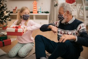 Little blonde girl receiving a Christmas present from her grandfather, both wearing a protective face mask, maintaining social distancing and thanking him for the present by bumping an elbow with him
